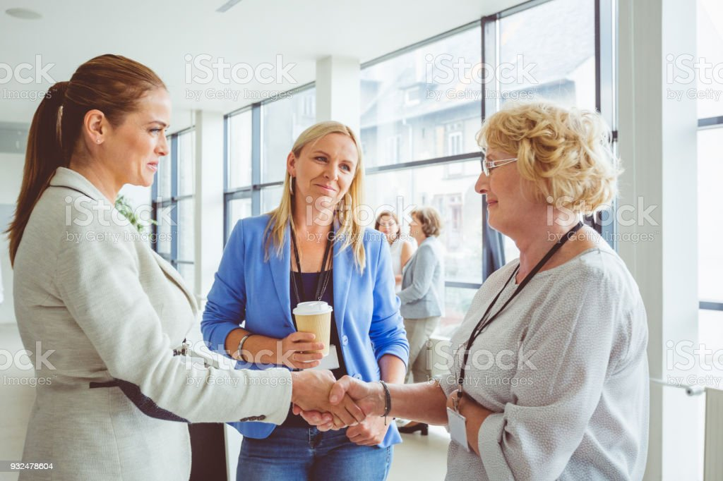 Women shaking hands during conference Senior woman shaking hand with young woman during seminar. Active Seniors Stock Photo