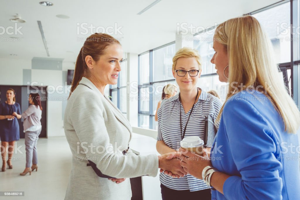 Women shaking hands during conference Mature woman shaking hand with young woman during seminar. Adult Stock Photo