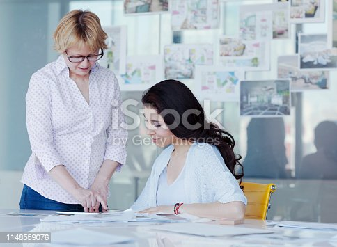 istock Women sharing ideas at table in design office 1148559076