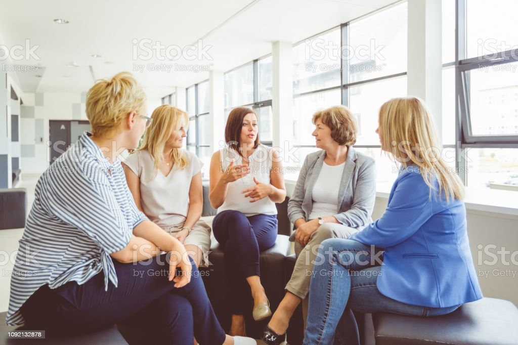 Women sharing their experience during training Woman sharing her experience with females sitting together. Group of women during a training session in office. Adult Stock Photo