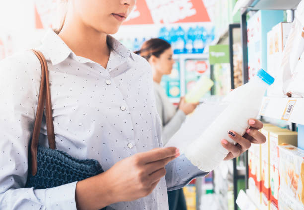 women shopping at the supermarket - nutrition label stock photos and pictures