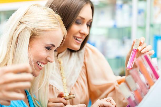 frauen shopping für make-up-produkte - drogerie stock-fotos und bilder