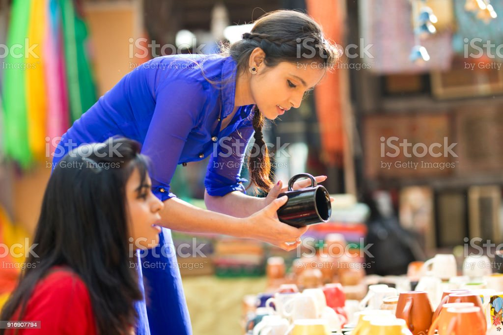 Women shopping for porcelain jug at street market stock photo
