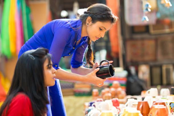 Women shopping for porcelain jug at street market stock photo