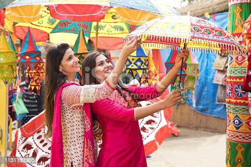 Indian women shopping for parasol at street market