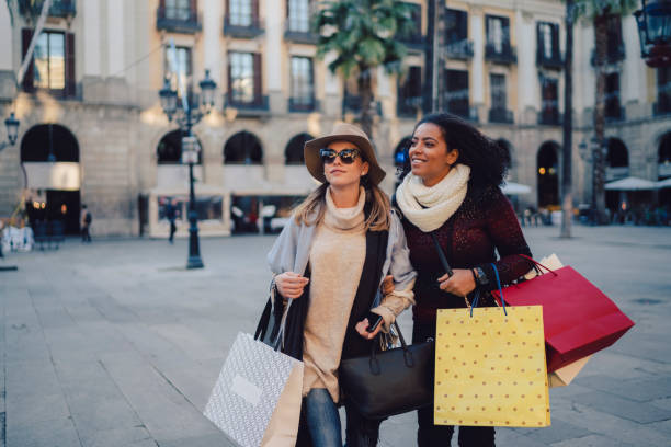 Women shopping in Barcelona Two women wearing paper bags in the city after shopping high society stock pictures, royalty-free photos & images