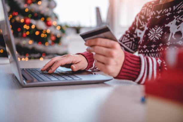 Women shopping online during christmas Women wearing red sweater shopping online and using credit card at home office holidays stock pictures, royalty-free photos & images