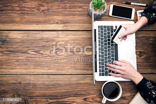 Women shopping online on wooden table with space on text
