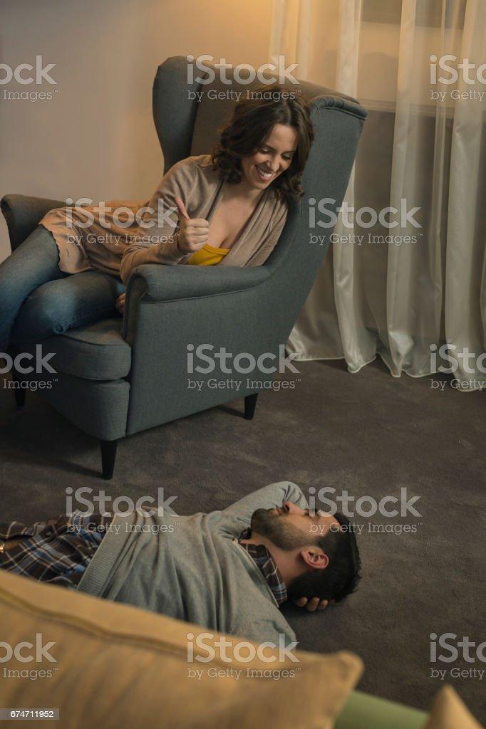 Women showing thumb up on man who sleeps on floor stock photo