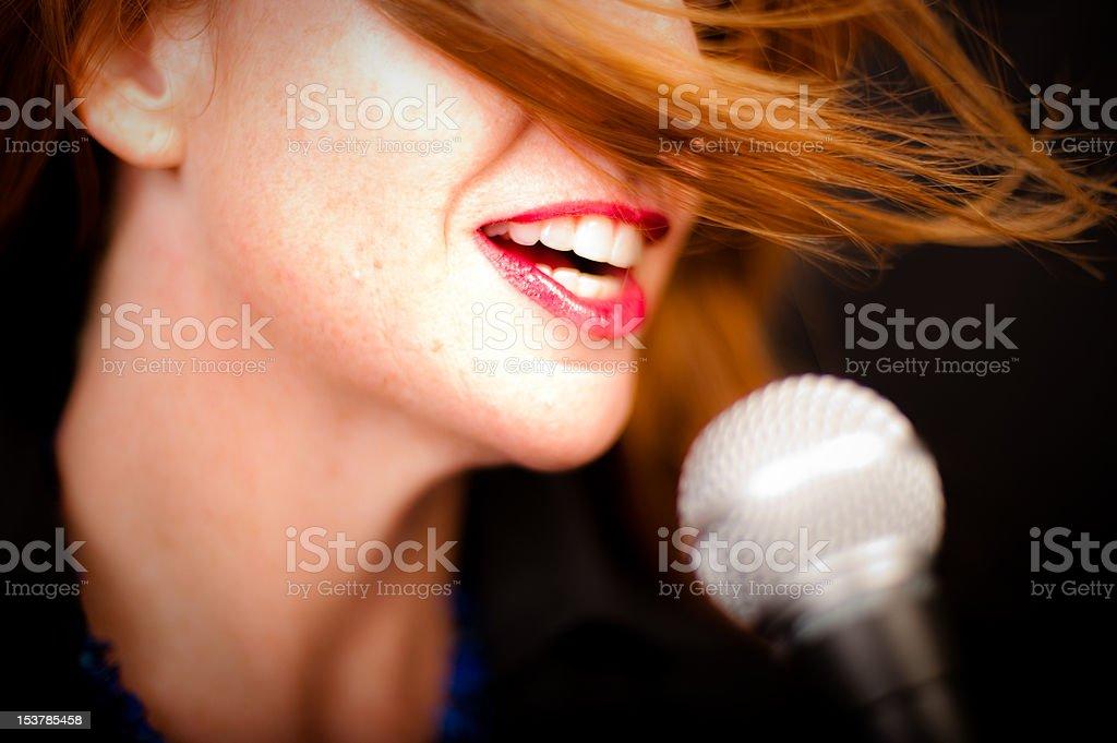 Women singing, talking into microphone stock photo