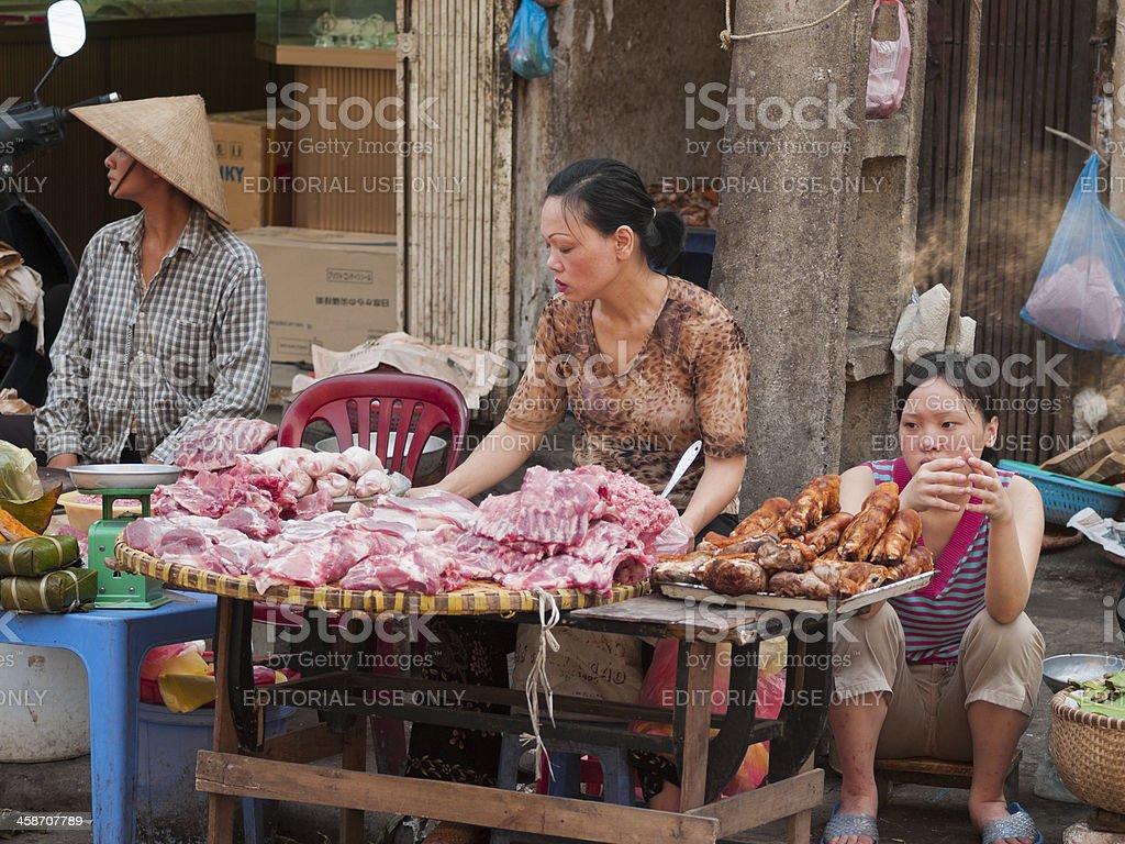 Women sit at a street-side stall , Hanoi, Vietnam royalty-free stock photo
