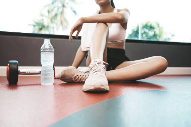 Women sit back and relax after exercise. There is a water bottle and dumbbells,selective focus stock photo