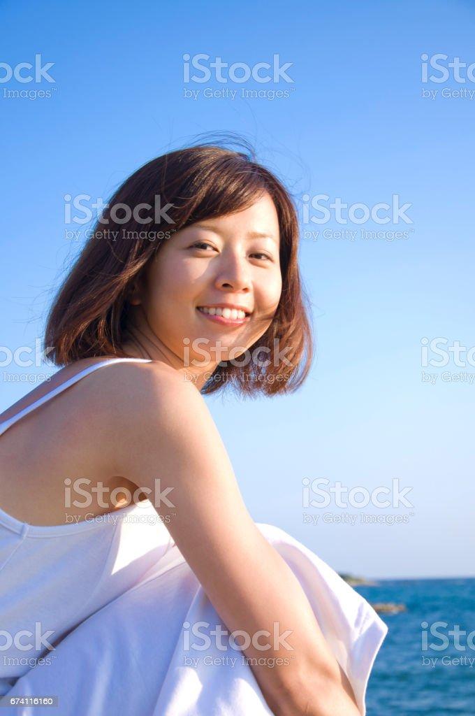 婦女坐在海岸上 免版稅 stock photo