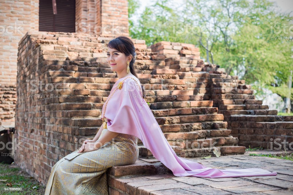 Women sit wearing traditional cloth Thailand or Thai dress in ancient city and walls background. stock photo