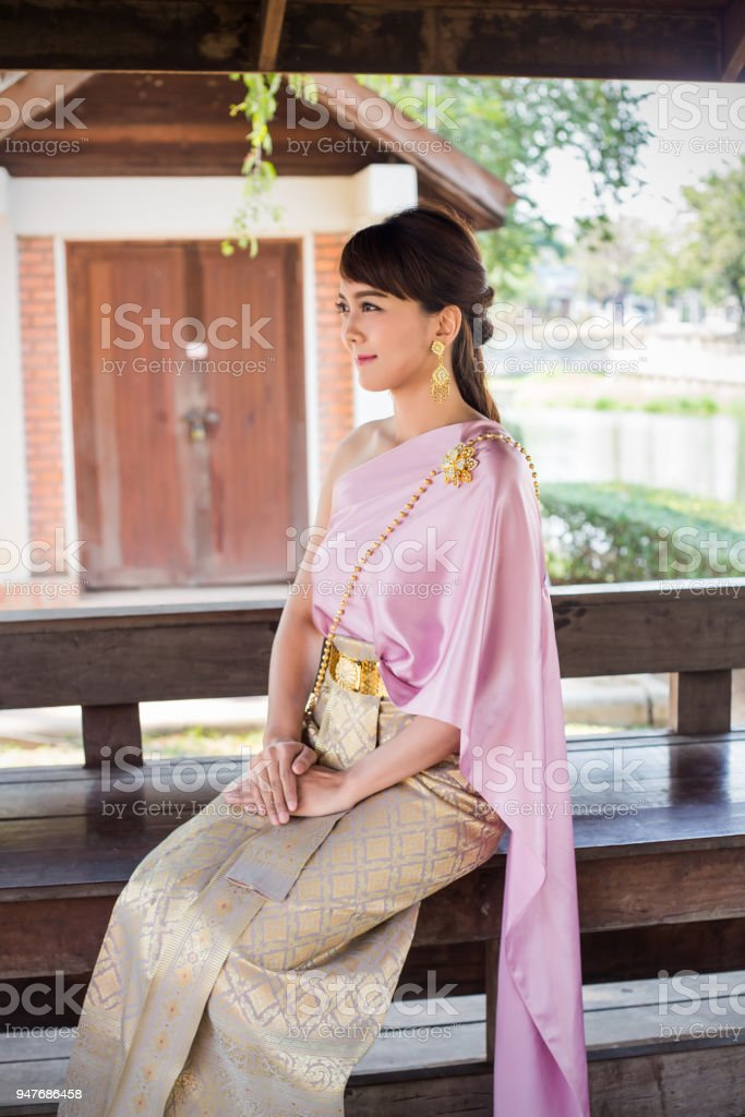 Women sit wearing traditional cloth Thailand or Thai dress in traditional Thai House. stock photo