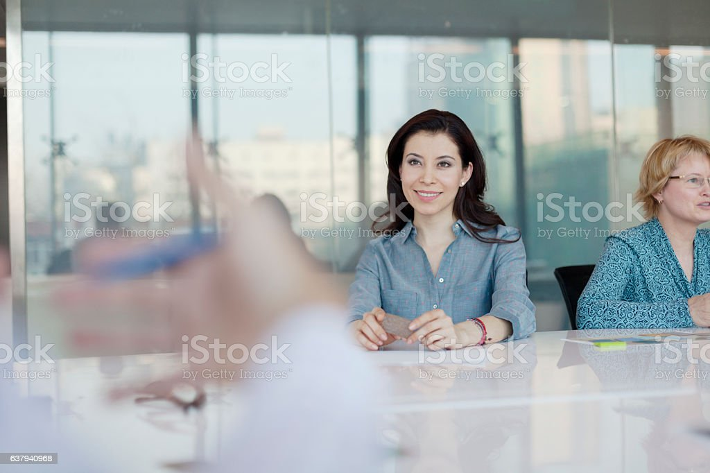 Women sitting at conference table in bright office stock photo