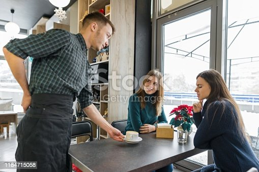597640822 istock photo Women sitting at the table with cup of coffee, and male barista 1184715058
