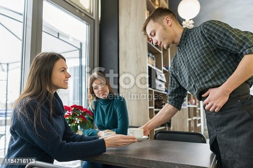 597640822istockphoto Women sitting at the table with cup of coffee, and male barista 1184716113