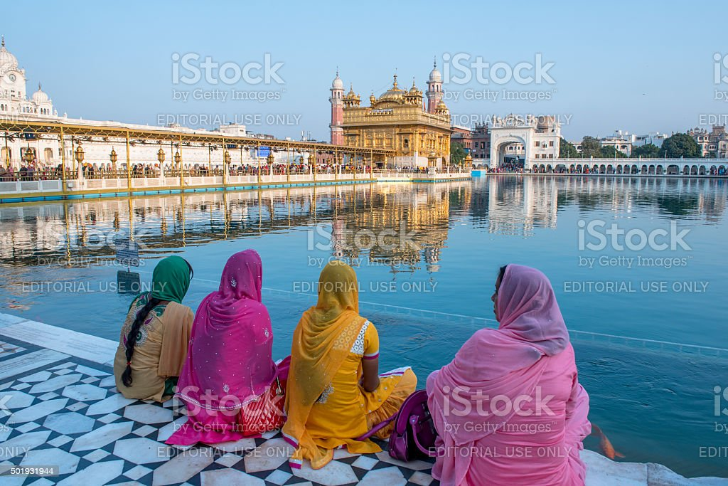 Women sitting in front of Golden Temple, Amritsar, India stock photo