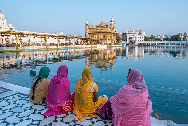 frauen sitzen vor der goldene tempel, amritsar, indien - goldener tempel stock-fotos und bilder