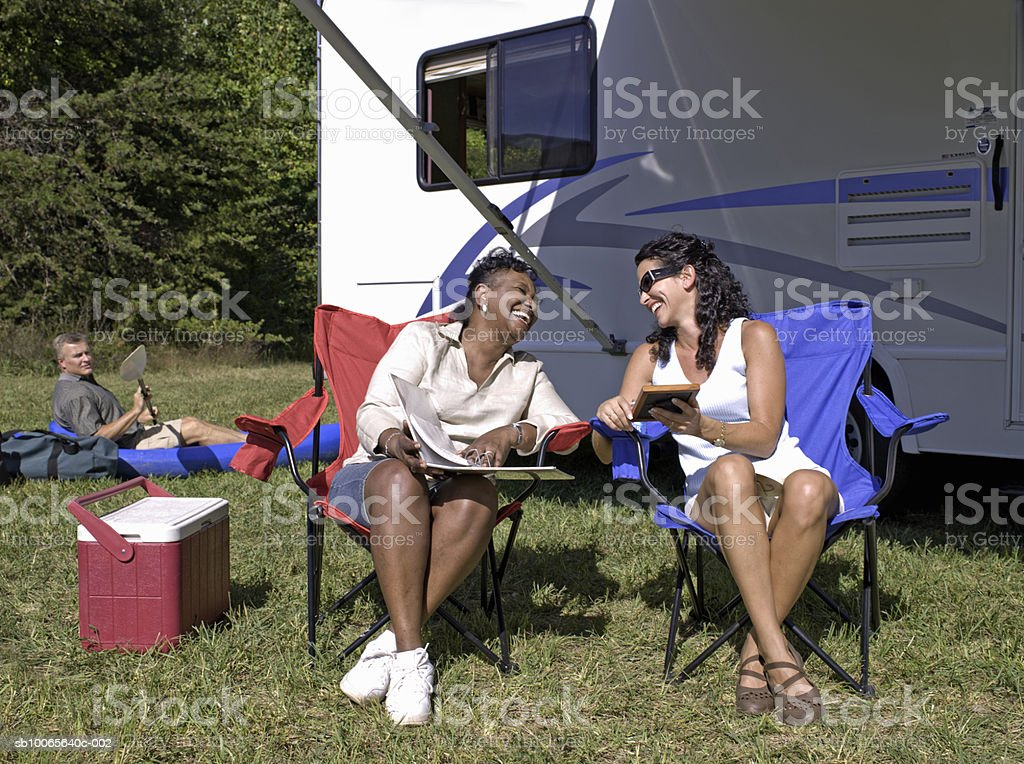 Women sitting on chair looking at photo album, man in kayak in background foto stock royalty-free