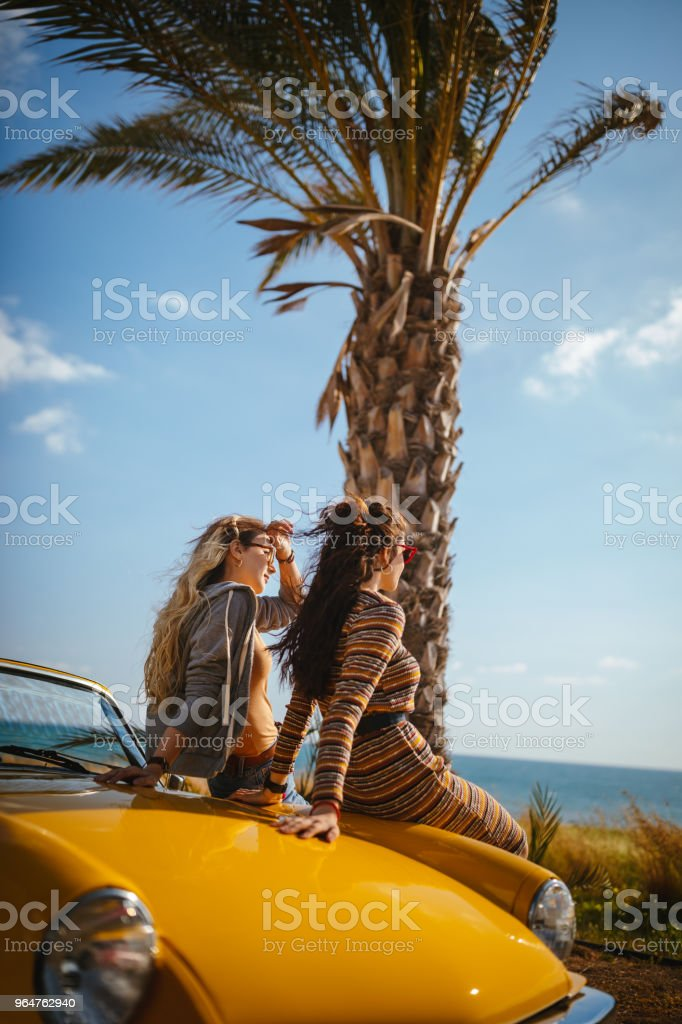 Women sitting on convertible car and looking at the sea royalty-free stock photo