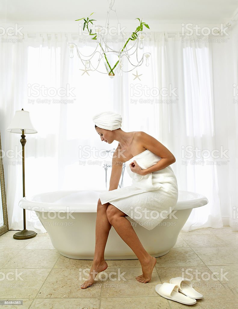 Women sitting on edge of bath feeling the water photo libre de droits