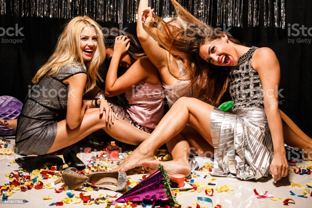 Women sitting on floor at party covered in confetti stock photo