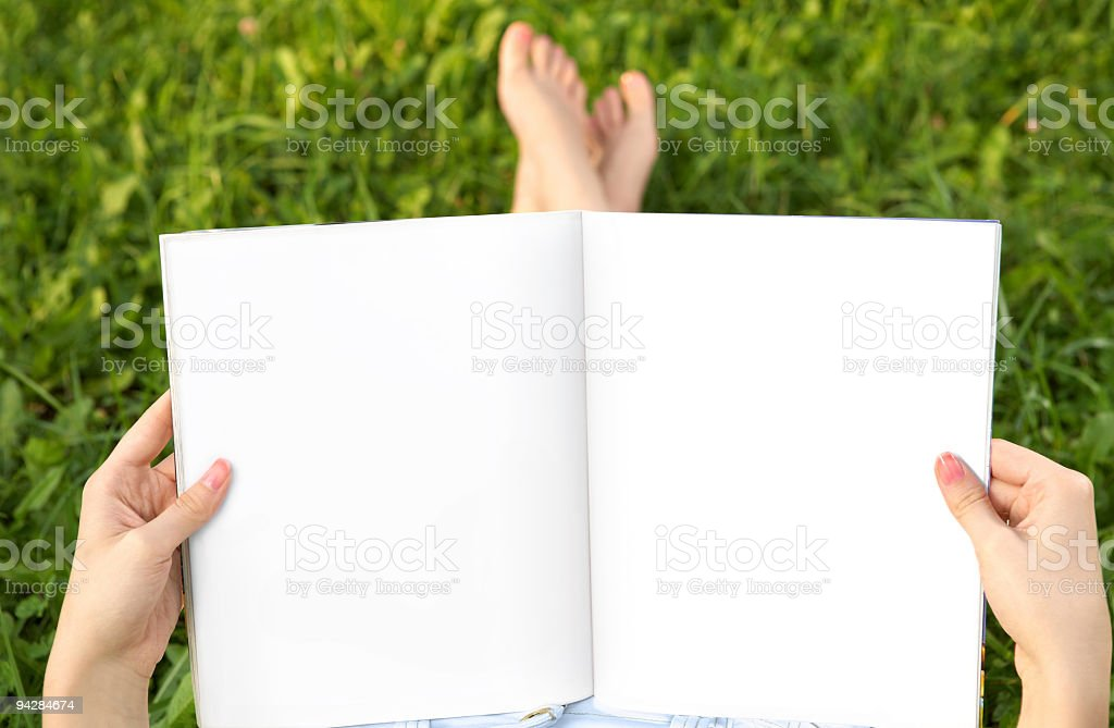 Women sitting on grass with blank journal pages stock photo