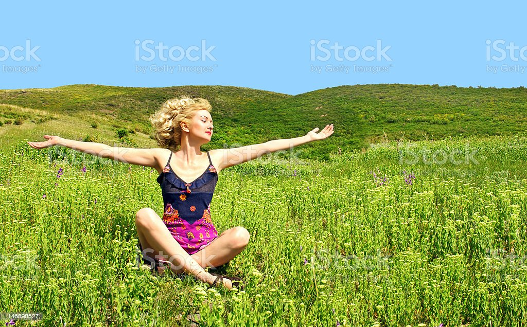 women sitting on grass with stretched hands stock photo