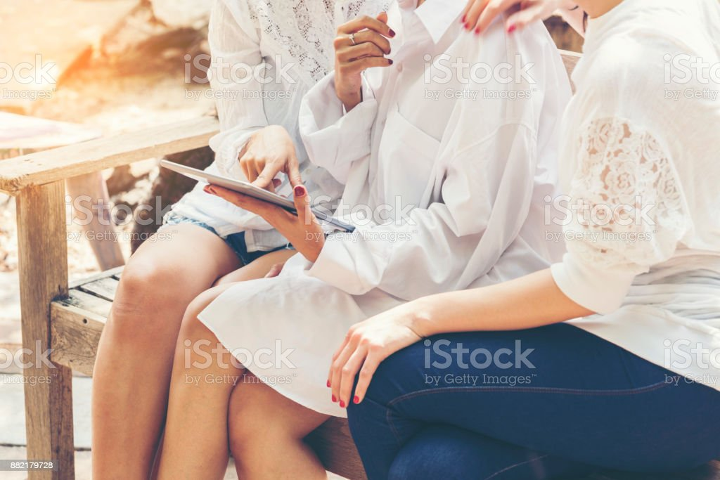 Women sitting on the wooden chair using tablet stock photo