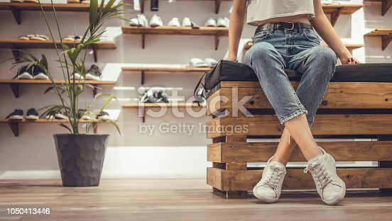 Close-up view image of women sitting with legs crossed trying on new sneakers in shopping center