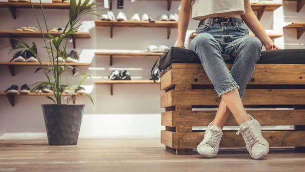 frauen sitzen mit gekreuzten beinen versucht auf neue turnschuhe im einkaufszentrum - sitzbank schuhe stock-fotos und bilder