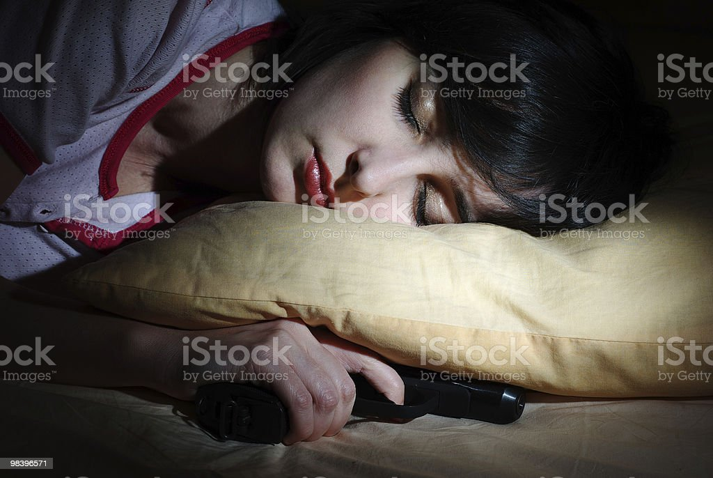 Women sleeps with gun under the pillow royalty-free stock photo