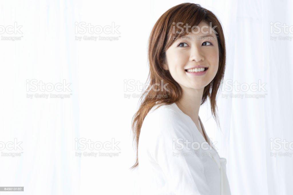 カーテン越しに微笑む女性 ストックフォト