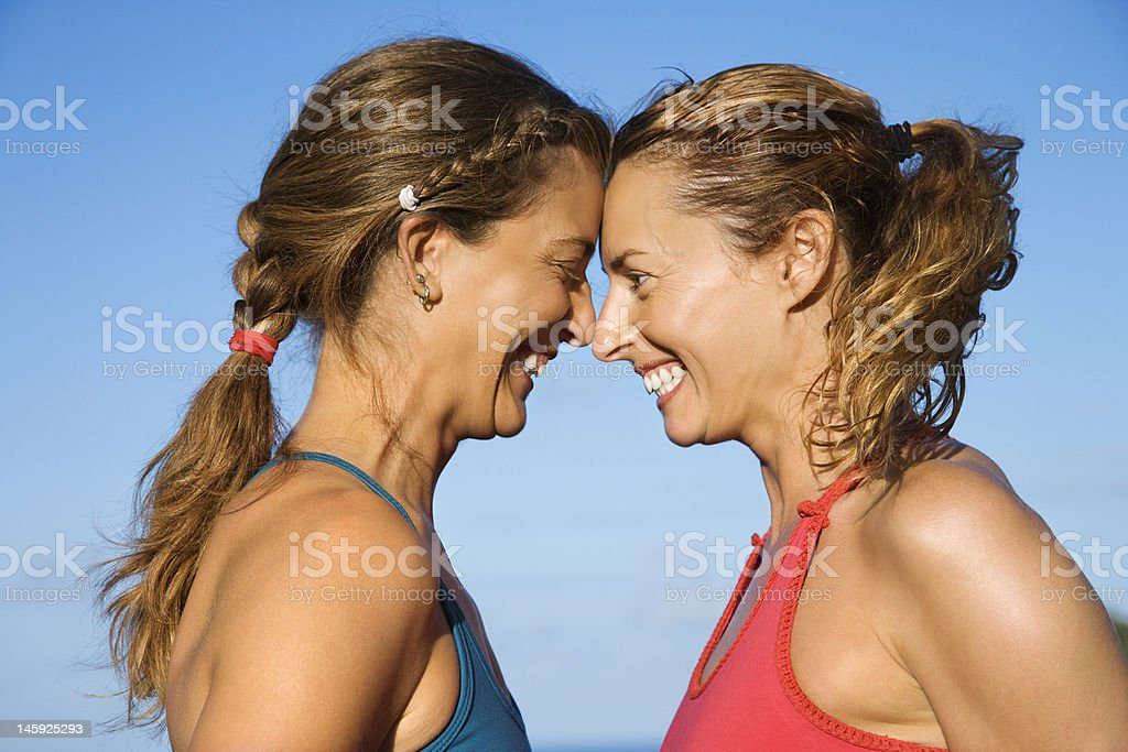 Women smiling with foreheads touching royalty-free stock photo