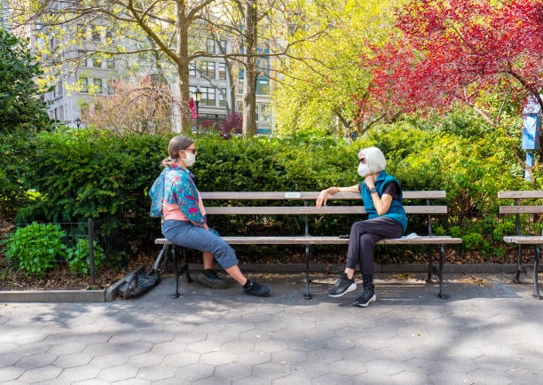 women social distancing and wearing face mask in new york city. - new normal foto e immagini stock