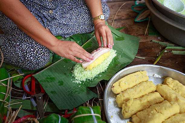 women southern Vietnam is package tet cakes Hochiminh City, Vietnam - February 5, 2016: women southern Vietnam is package tet cakes for the Lunar New Year. Tet cakes and chung cakes made from glutinous rice, meat, green beans, cover with banana leaves, and tie with bamboo string. They are Vietnamese traditional dishes annually stock pictures, royalty-free photos & images