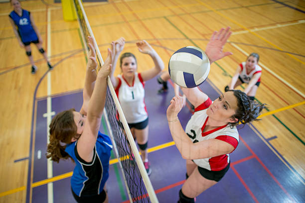 women spiking and blocking a volleyball - volleyball sport stock photos and pictures
