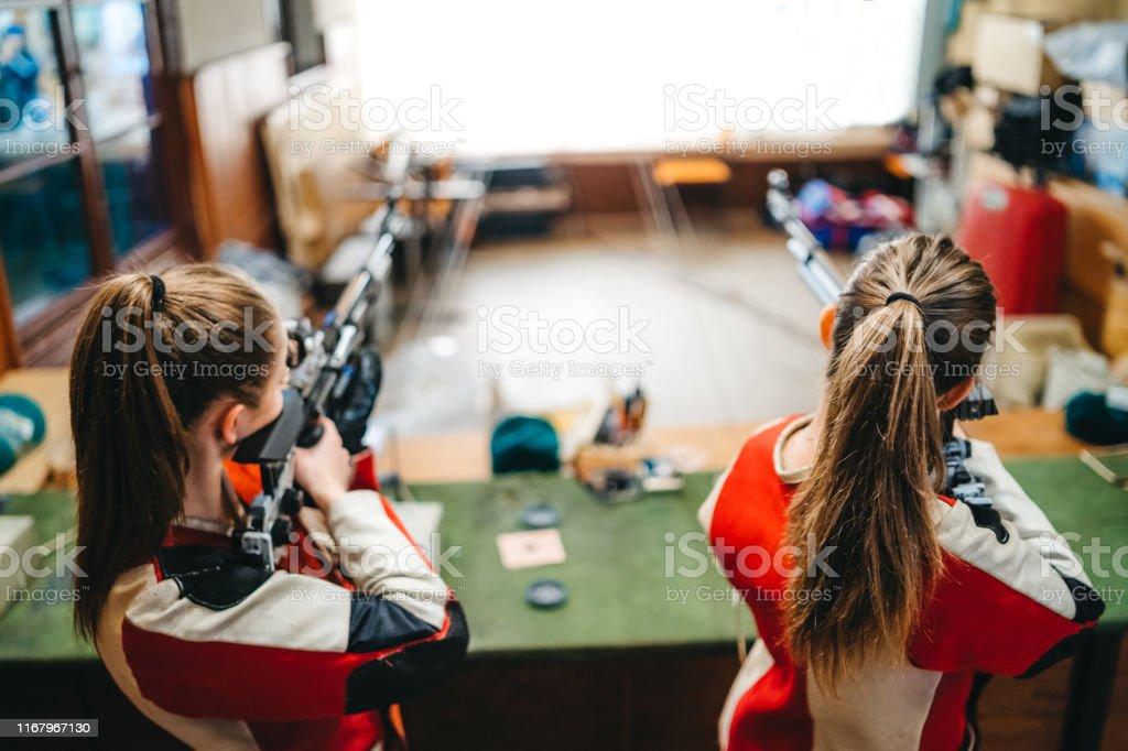 Two young caucasian women having sport shooter training.