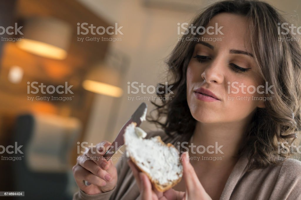 Women spreading cream cheese on slice of bread and eating at home