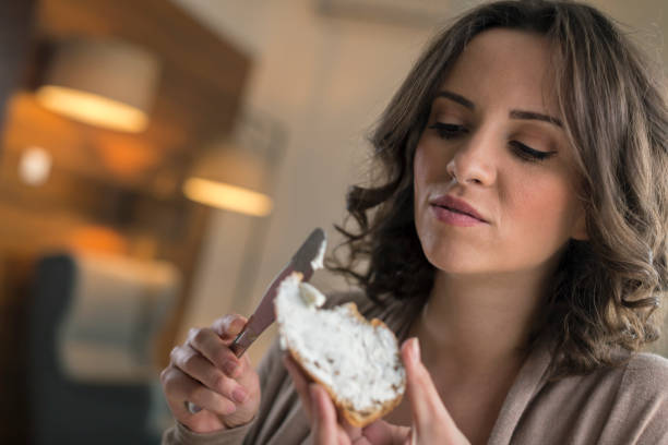Women spreading cream cheese on slice of bread and eating at home stock photo