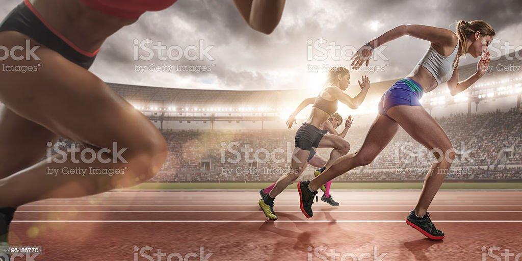 Mujeres Sprinters durante la raza en la pista de atletismo al aire libre en la Arena - foto de stock