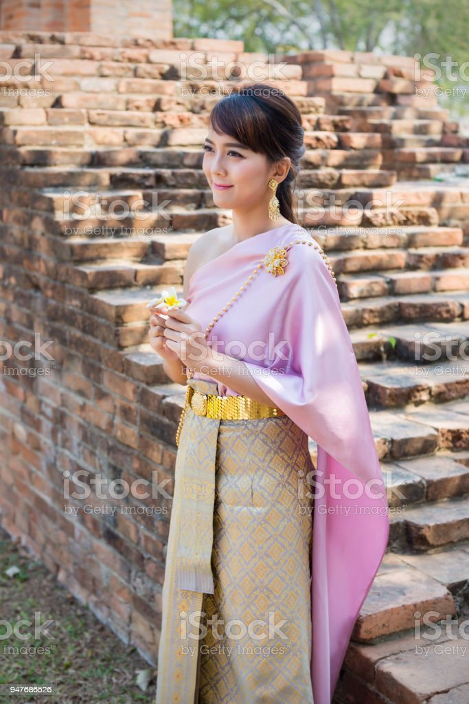 Women stand wearing traditional cloth Thailand or Thai dress in ancient city and walls background. stock photo