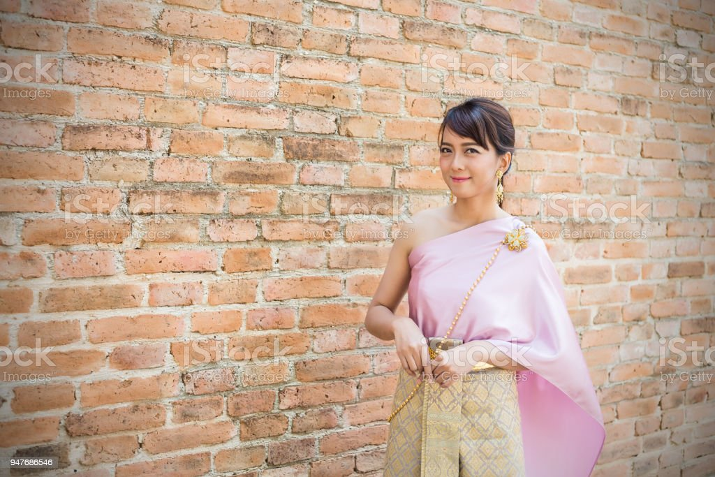 Women stand wearing traditional cloth Thailand or Thai dress with ancient walls background stock photo