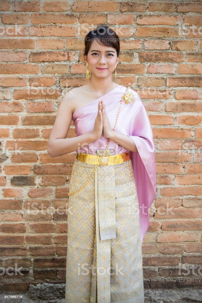 Women stand wearing traditional cloth Thailand or Thai dress with ancient walls background. Welcome or Sawasdee stock photo