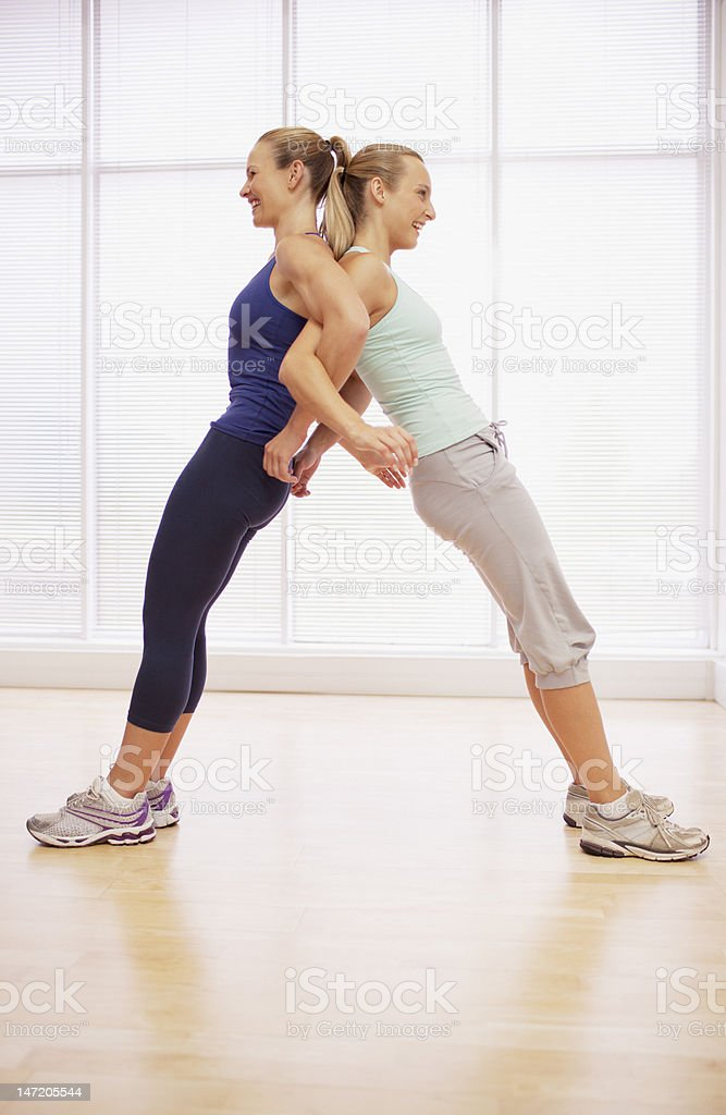 Women standing back to back in fitness studio stock photo