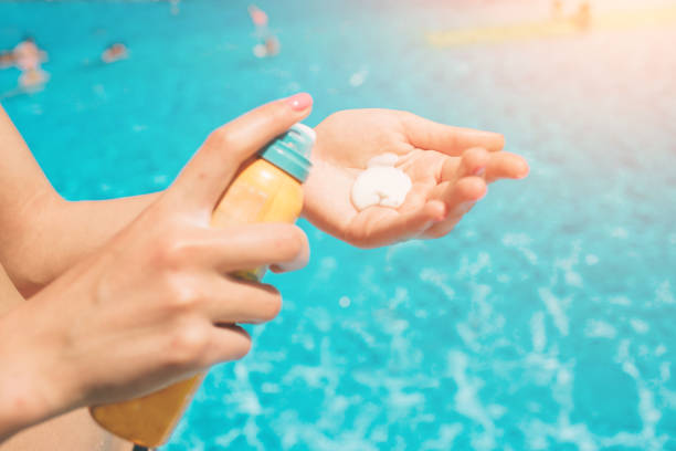 women standing on the beach and using suncream. close up of women hands receiving sunblock cream lotio women standing on the beach and using suncream. close up of women hands receiving sunblock cream lotio. suntan lotion stock pictures, royalty-free photos & images