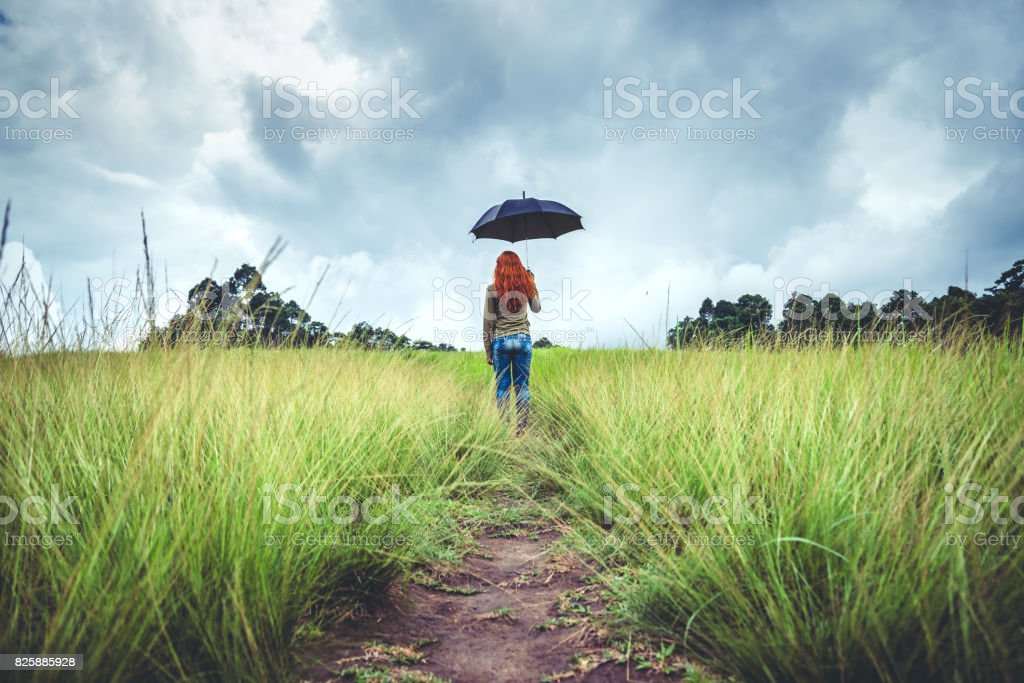 Women standing umbrella On the green meadow in the rainy season. Asian women stock photo