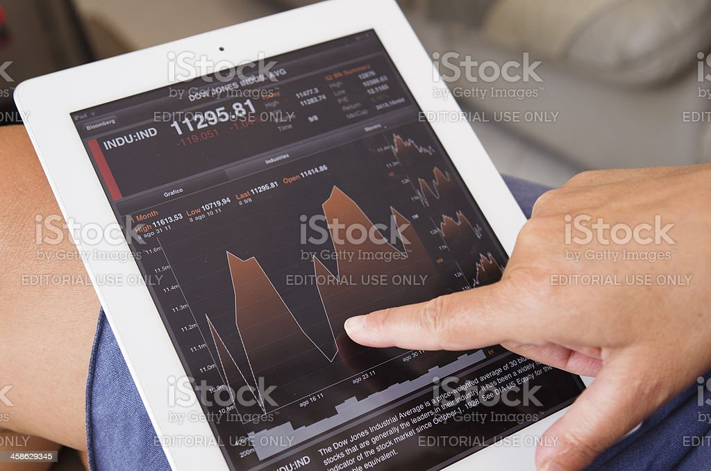 Women Stock analytics check graph on Bloomberg Ipad app royalty-free stock photo